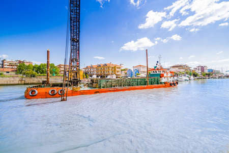 dredging: Boat dredging while fishing boats moored in the port channel of a town on the Adriatic Riviera in Emilia Romagna in Italy Stock Photo