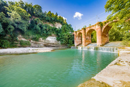 fourteenth: Fresh waters of river running under fourteenth century bridge in masonry in a small village in the hills in Romagna, Italy Stock Photo