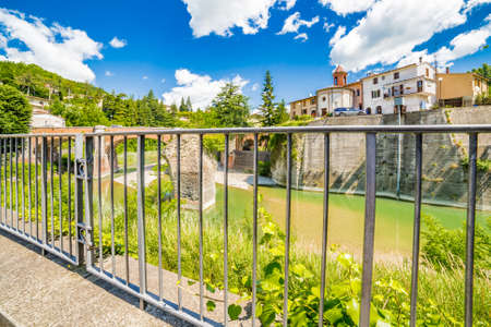 savio: waters of river running around rocky stack and under twelfth century bridge seen through an iron railing in a small village in the hills in Romagna, Italy Stock Photo