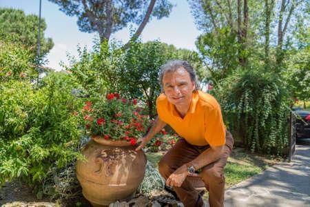 crouching: Man crouching next to a pot of red petunias Stock Photo