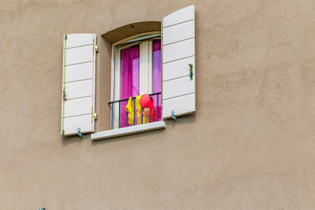 hung: window with women swimsuits hung out to dry