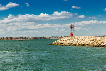 powered: red metal lighthouse powered by solar panel on a pier with the Adriatic coast and sea in the background Stock Photo