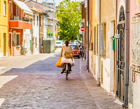 brightly: a woman on a bicycle with shopping bags on the streets along the cheerful brightly colored houses of a fishing charming village in Romagna, Italy