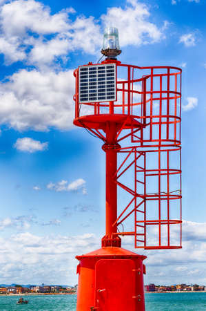 powered: red metal lighthouse powered by solar panel with the Adriatic coast and sea in the background