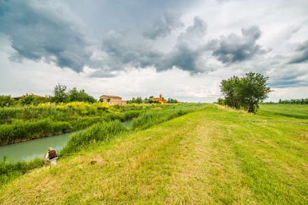bucolic: old fisherman fishing in a river running along an eighteenth century church in bucolic landscape of the countryside of Romagna in Italy Stock Photo