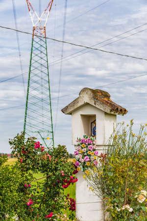 votive: Votive Catholic shrine under high voltage pylons Stock Photo