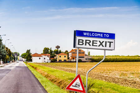instability: a fake sign with welcome to brexit, abbreviation of Britain exit from European Union, with warning road sign about dangerous verges Stock Photo