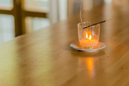 new age: a stick of burning incense held above a glass with candle