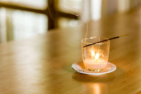 held: a stick of burning incense held above a glass with candle