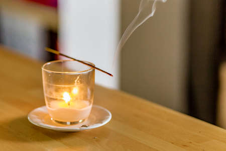meditation room: a stick of burning incense held above a glass with candle