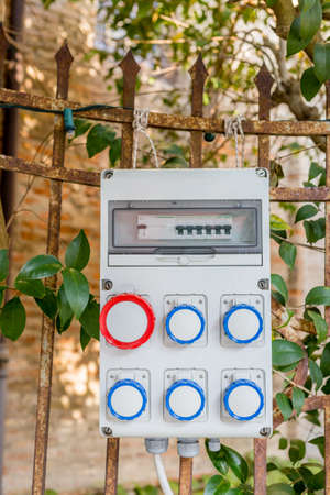 to grate: electrical panel hung on the grate of a garden
