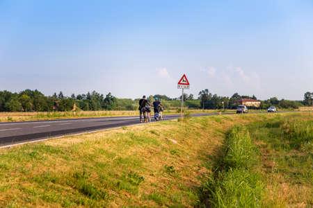 cansancio: ciclistas que recorren en una carretera con la bicicleta a su lado