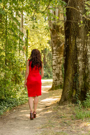 rear view of woman in red, high heels and cocktail dress who ventures into a path among trees