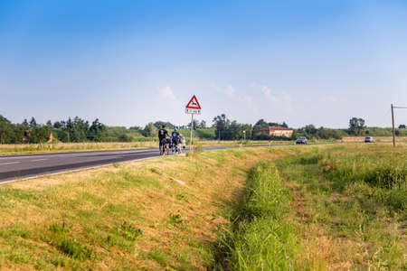cansancio: cyclists walking on a highway with the bicycle at their side Foto de archivo