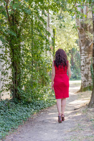 ventures: rear view of woman in red, high heels and cocktail dress who ventures into a path among trees
