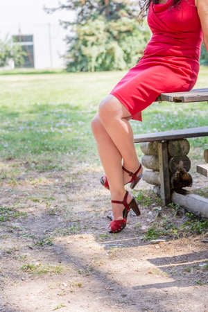 40 year old: beautiful and sinuous crossed legs of over 40 woman, bandaged by a red dress with high-heeled sandals Stock Photo