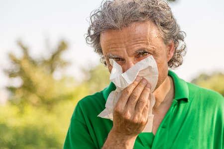 Hombre de mediana edad con el pelo largo y gris y el hombre de barba de tres días se suena la nariz con una toalla de papel blanco