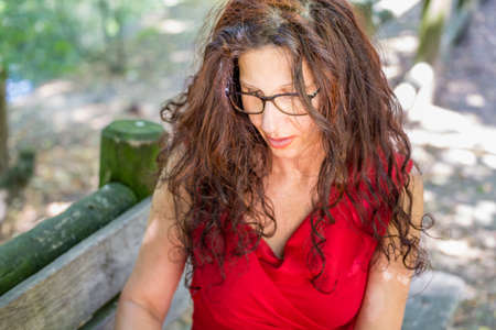 30 to 40 year old: gorgeous middle-aged woman in a red dress and long brown wavy hair is looking down wearing a pair of nerdy eyeglasses