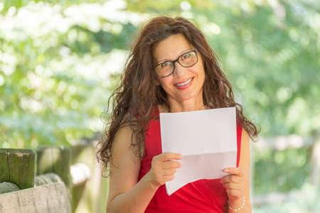 40 year old woman: gorgeous middle-aged woman in a red dress and long brown wavy hair is reading a paper and smiling while wearing a pair of nerdy eyeglasses in a garden Stock Photo