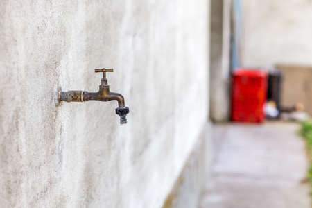 wastage: rusty old faucet on wall