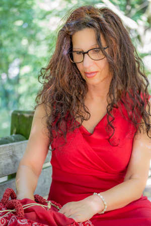 50 60 years: gorgeous middle-aged woman in a red dress and long brown wavy hair is looking for something in the bag, wearing a pair of nerdy eyeglasses