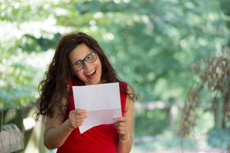 40 year old woman: gorgeous middle-aged woman in a red dress and long brown wavy hair is reading a paper and laughing with a grimace of caricatured enthusiasm while wearing a pair of nerdy eyeglasses in a garden Stock Photo