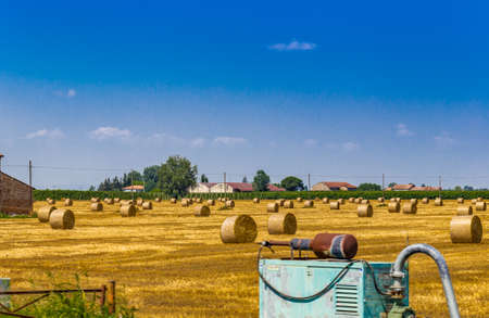 bucolic: round hay bales in a harvested field near a country farmhouse and pump for irrigation in the foreground, rural and bucolic atmosphere of a hot summer day