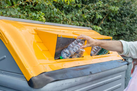 man putting plastic waste in the appropriate recycling bin