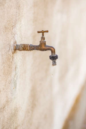 wasting: rusty old faucet drips wasting water Stock Photo