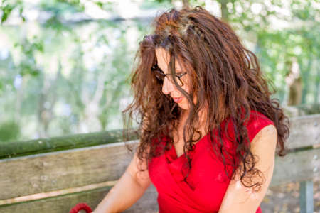 40 year old woman: gorgeous middle-aged woman in a red dress and long brown wavy hair is looking down wearing a pair of nerdy eyeglasses