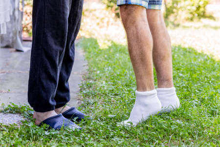 discreet: affection between two men, seen in a very discreet manner through the position of their legs, outstretched towards each other as in the classic iconography of the kiss Stock Photo