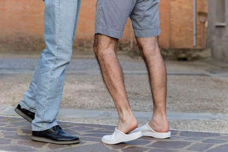iconography: affection between two men, seen in a very discreet manner through the position of their legs, outstretched towards each other as in the classic iconography of the kiss Stock Photo