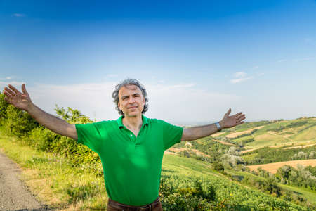 spreads: tired mature man spreads his arms upward while a quiet, hilly countryside is in background, it is time to rest Stock Photo