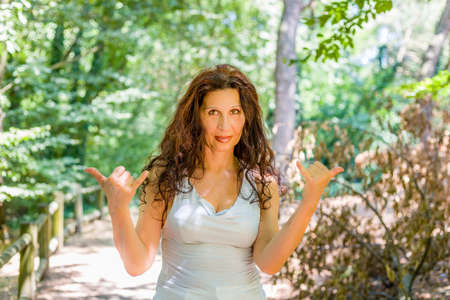 Cierre de tetona mujer madura con clase sonriendo a la cámara mientras hace la muestra de Shaka bienvenida contra el fondo verde jardín, con espacio de copia