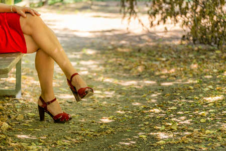 30 to 40 year old: beautiful and sinuous crossed legs of over 40 woman, bandaged by a red dress with high-heeled sandals Stock Photo