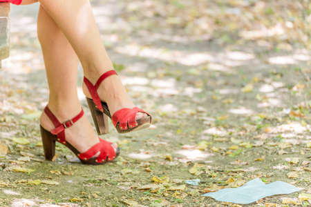 sinuous: beautiful and sinuous crossed legs of over 40 woman, with high-heeled red sandals