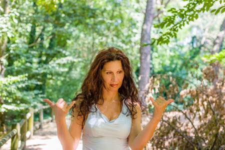 tetona: Primer plano de mujer madura con clase tetona al tratar de hacer señal de shaka de bienvenida contra el fondo verde jardín con espacio de copia