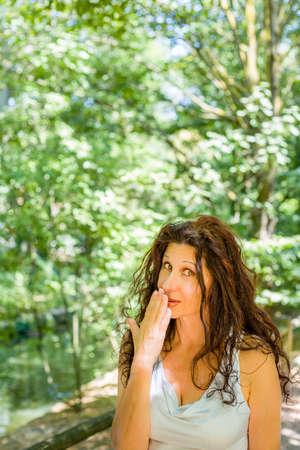 busty: Cierre de tetona mujer madura con clase sonriendo a la cámara mientras se cubre la boca con la mano contra el fondo verde del jardín con espacio de copia