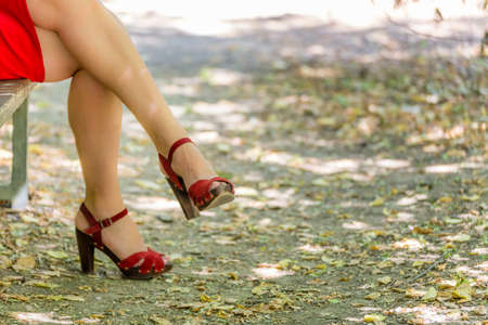 50 60 years: beautiful and sinuous crossed legs of over 40 woman, bandaged by a red dress with high-heeled sandals Stock Photo