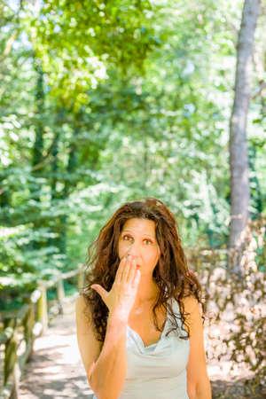 tetona: Primer plano de mujer madura con clase tetona tapándose la boca con la mano contra el fondo verde jardín con espacio de copia