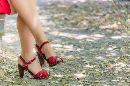 bandaged: beautiful and sinuous crossed legs of over 40 woman, bandaged by a red dress with high-heeled sandals Stock Photo