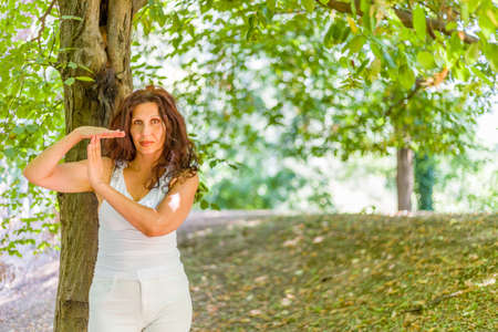 buxom: Buxom mature woman in white dress showing time out gesture, over green background