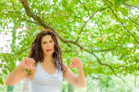 tetona: Descontento con clase tetona mujer madura que da los pulgares hacia abajo gesto mirando con expresi�n negativa en la c�mara contra el fondo verde jard�n con espacio de copia Foto de archivo