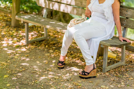 legs of woman sitting on bench in white trousers and high platform shoes, knees touching each other