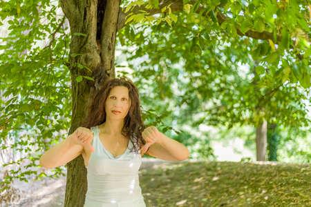 busty: tetona con clase Mujer madura que da los pulgares abajo gesto mirando a la cámara contra el fondo verde jardín con espacio de copia