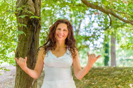 busty: Cierre de tetona mujer madura con clase sonriendo a la cámara mientras hace la muestra de Shaka bienvenida contra el fondo verde jardín, con espacio de copia