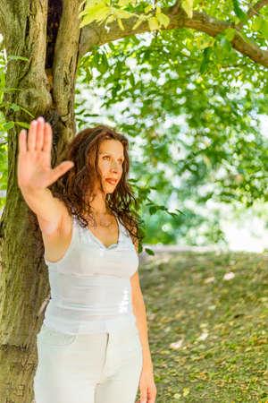busty: Parar y hablar con la mano el gesto de mujer madura con clase tetona con los sentimientos negativos contra el fondo verde jardín con espacio de copia