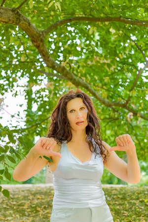 busty: Descontento con clase tetona mujer madura que da los pulgares hacia abajo gesto mirando con expresión negativa en la cámara contra el fondo verde jardín con espacio de copia Foto de archivo