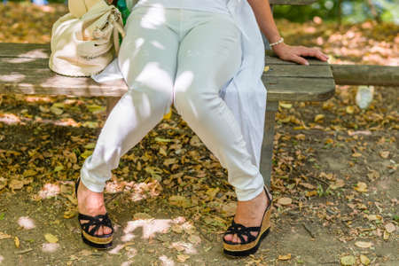distension: legs of woman sitting on bench in white trousers and high platform shoes, knees touching each other