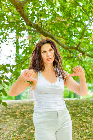 busty: Unhappy busty classy mature woman giving thumbs down gesture looking with negative expression at the camera against green garden background with copy space